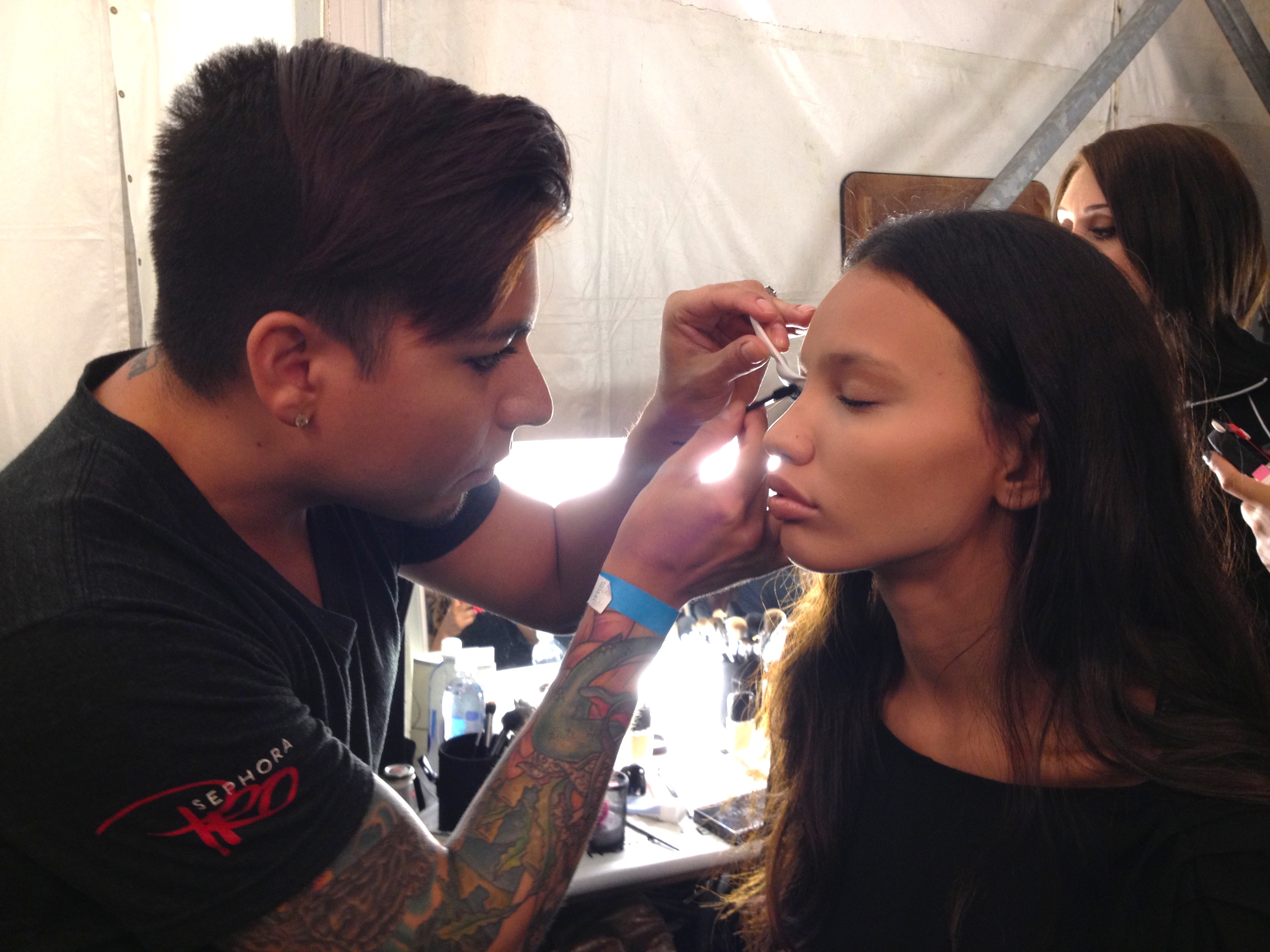 A makeup artist using Val's fan brush technique on the lashes of a model backstage at BCBGMAXAZRIA.