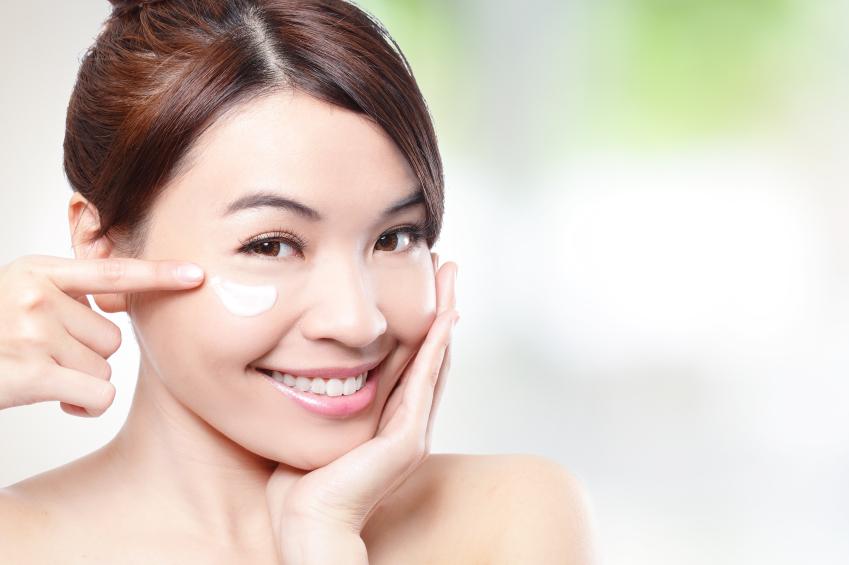 Beauty young woman applying cosmetic cream