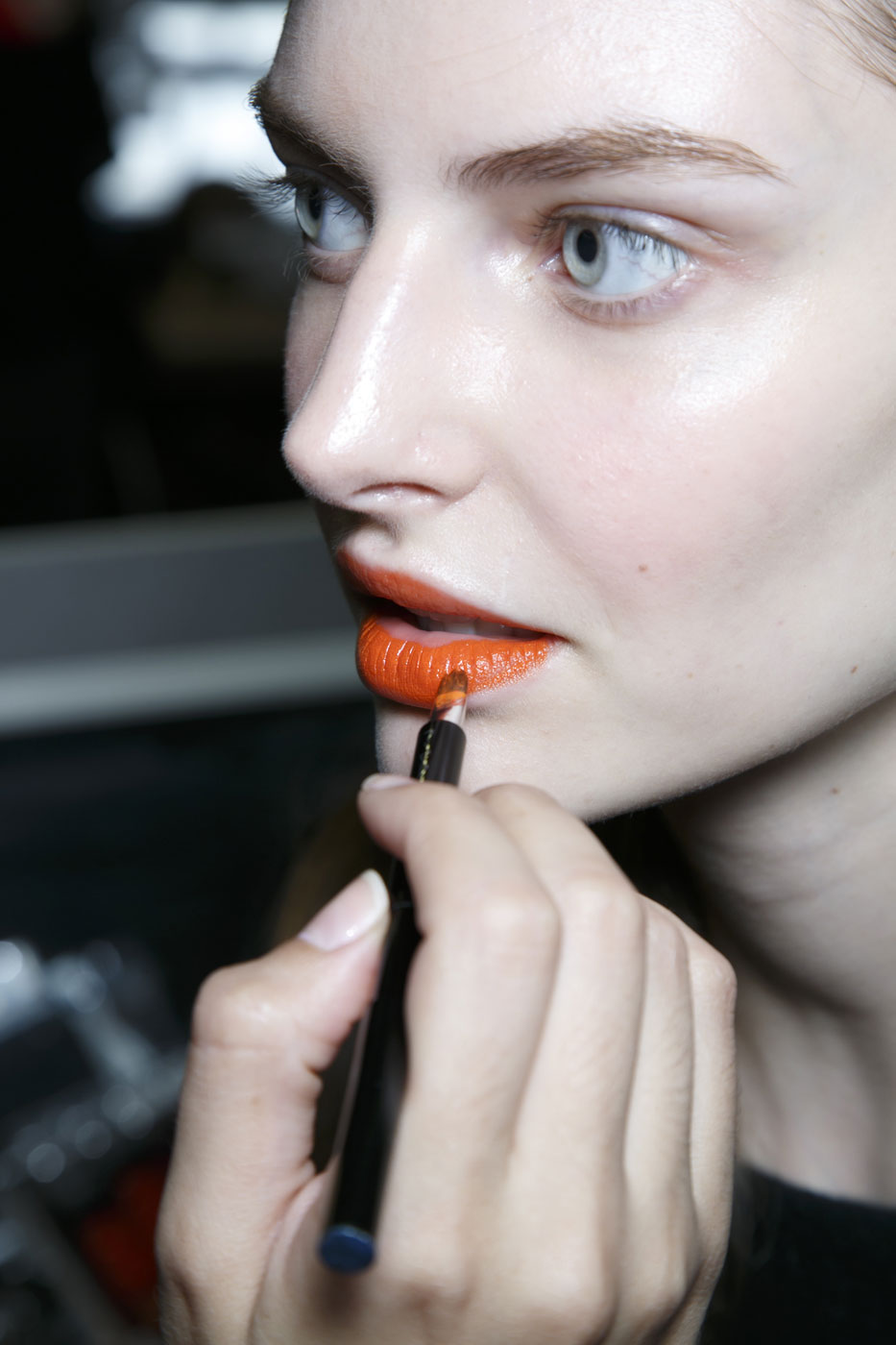 girl applying orange lipstick